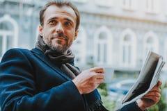 Den positiva mannen har den varma drinken och läser papper utomhus fotografering för bildbyråer