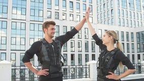 Den positiva mannen och kvinnan som bär EMS-dräkter, rejoycing på bra resultat lager videofilmer