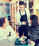 Den positiva servitrisportionen bakar ihop och bakelse för flickor royaltyfri fotografi