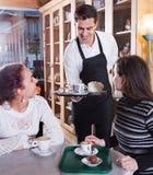 Den positiva servitrisportionen bakar ihop och bakelse för flickor royaltyfri bild