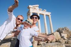 Den positiva unga familjen tar ett foto för sammersemesterselfie på myra Arkivfoto