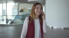 Den positiva unga flickan i elegant kläder talar på smartphonen på flygplatsen stock video