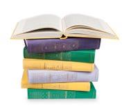 Den öppna boken på en hög av tappning bokar i mångfärgade räkningar Arkivfoto