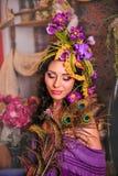Den pråliga brunetten med lilor blommar i hennes hår Arkivfoto