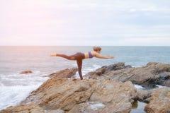 Den praktiserande yogasolnedgången för kvinna på stranden arkivbilder