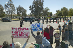 Den presidents- motorcaden med presidenten George W Bush förbi politiska anti--Bush samlar med tecken, att läst ifrågasätta Bush  Arkivbild