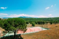 Den privata tennisbanan på villan vid havet, Montenegro, annons Royaltyfri Bild