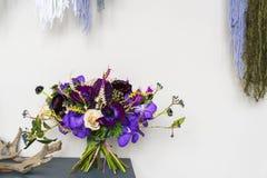 Den purpurfärgade bröllopbuketten är på tabellen i inre Gifta sig trender Royaltyfria Bilder