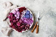 Den purpurfärgade Buddhabunken med spirala morötter, blomkålen, beta, löken, potatis, strimlade röd kål, radicchiosallad, kalamat Arkivfoto