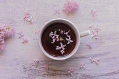 Den purpurfärgade lilan blommar och kopp te på ljus träslags tvåsittssoffa för bakgrund för bakgrundsteatime/vår på garnering för arkivbild