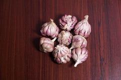 Den purpurfärgade vitlöken på matlagningtabellen arkivfoton