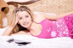 In den Pyjamas mit dem Tabletten-PC-Computer, der auf dem weißen Bett liegt u. schöne attraktive blonde Frau der grünen Augen des Lizenzfreie Stockfotografie