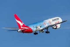 Den Qantas Boeing 767 trafikflygplanet med special teckning som främjar Disney, hyvlar filmen som tar av från Sydney Airport Arkivfoton