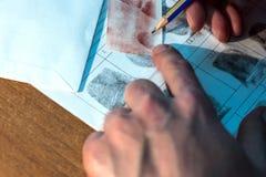 Den rättsmedicinska avläsaren jämför fingeravtryck Närbild av manhänder med en blyertspenna Arkivbild