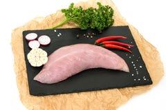 Den rå kalkonköttfilén, fegt bröst, bantar vitt kött på ett svart stenbräde, med varm laga mat mat, isolaten, vit bakgrund arkivbild