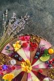Den rå strikt vegetarian bakar ihop med frukt och frö som dekoreras med blomman, produktfotografi för bakelser royaltyfri bild