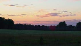 Den röda aerostaten i formen av en hjärta står på solnedgången i fälten stock video