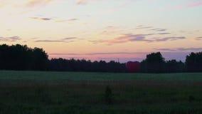 Den röda aerostaten i formen av en hjärta står på solnedgången i fälten arkivfilmer