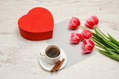Den röda asken i hjärtaform, rosa tulpan, grå färger täcker, och ett kaffe rånar ljus tabell Arkivfoto