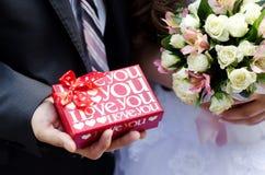 Den röda asken med förälskelse i händerna av brudgummen Royaltyfria Bilder