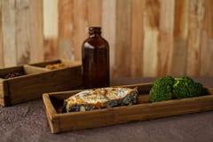 Den röda bakade fisken med broccoli, i en träposyda, en användbar lunch, en matställe, en banta, mat arkivbild