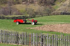 Den röda behind traktoren står i gårdsplanen Arkivfoton