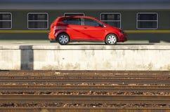 Den röda bilen på järnväg posterar plattformen Fotografering för Bildbyråer