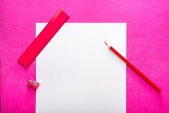 Den röda blyertspennan med vässaren, linjalen och vitbok täcker på röd bakgrund Plan design Kontorshjälpmedel Royaltyfri Foto
