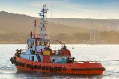 Den röda bogserbåten är kommande på Black Sea Arkivfoto