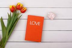 Den röda bokförälskelsen ligger på en vit tabell Blommatulpan och gåva Royaltyfria Bilder