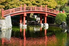 Den röda bron över en man gjorde dammet, den japanska kamratskapträdgården, San Jose, San Francisco Bay område, Kalifornien arkivfoton