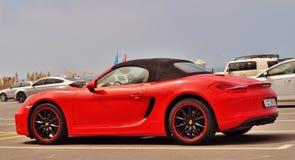 Den röda cabrioleten Porsche parkerade framme av stranden Royaltyfria Bilder