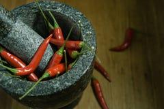 den röda chili är i mortelstenen Arkivbilder