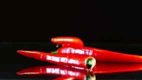Den röda chili faller långsamt på tabellen 4 peppar på köksbordet Mycket kryddig mat arkivfilmer