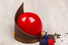 Den röda chokladglasyrkakan på tabellen Arkivfoton