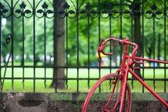 Den röda cykeln på staket av det gammalt parkerar Arkivfoton