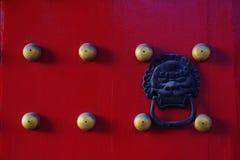 Den röda dörren med mässing spikar Arkivbilder