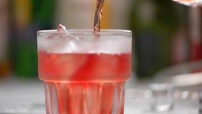 Den röda drycken häller långsamt lager videofilmer