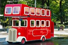 Den röda dubbeldäckarebussen i stad parkerar royaltyfria bilder