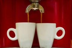 Den röda espressomaskinen häller kaffe in i två koppar Arkivfoto
