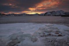 Den röda färgen av himlen och den djupfrysta sjön Arkivfoto