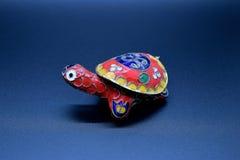 Den röda feng-shuisköldpaddan färgade metall med det avtagbara ryggsköldskalet för smycken som sätter in på mörk bakgrund royaltyfri foto