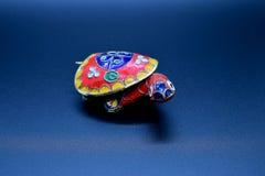 Den röda feng-shuisköldpaddan färgade metall med det avtagbara ryggsköldskalet för smycken som sätter in på mörk bakgrund royaltyfri bild