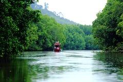 Den röda fiskebåten kör till kanalen av nytt salt vatten till den djupa mountaen arkivfoto