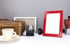 Den röda fotoramen, den retro kameran och kaffe lägger in med koppen kaffe arkivbilder