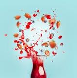 Den röda fruktsaft- eller smoothiedrinken hälls ut ur glasflaskan med färgstänk- och bäringredienser på turkosbakgrund, främre si royaltyfri bild