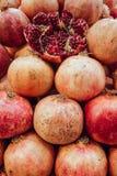 Den röda fruktsaftgranatäpplet på mörk bakgrund den öppna frukten av en granatäpple ligger på en kulle av granatäpplen arkivbilder