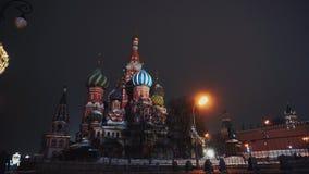 Den röda fyrkanten, en ensam grabb går förbi Kreml och Basil Church, vintern, natt arkivfilmer