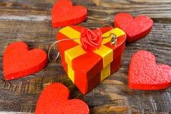 Den röda gåvaasken i formen som den har format hängeträhäftklammermataren med diamanten, henne, står på en träbakgrund som omges  royaltyfri fotografi