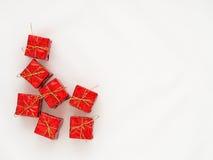 Den röda gåvaasken med det guld- bandet på vit isolerade bakgrund Arkivfoto